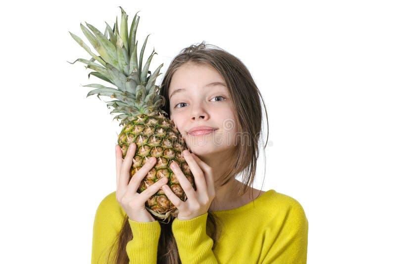 A moça encantador pressiona para enfrentar o grande abacaxi maduro fotos de stock royalty free