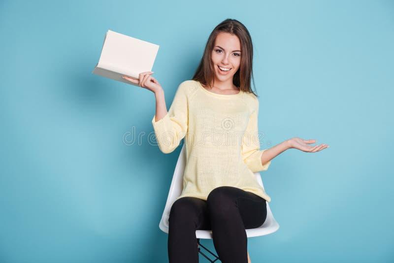 Moça engraçada com um livro sobre o fundo azul fotografia de stock royalty free