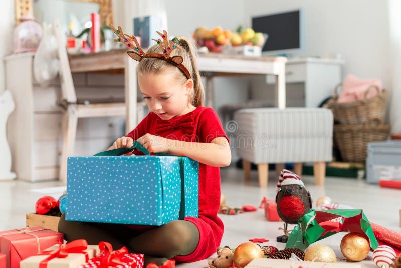 Moça entusiasmado super bonito que abre o grande presente de Natal ao sentar-se no assoalho da sala de visitas Tempo cândido do N foto de stock