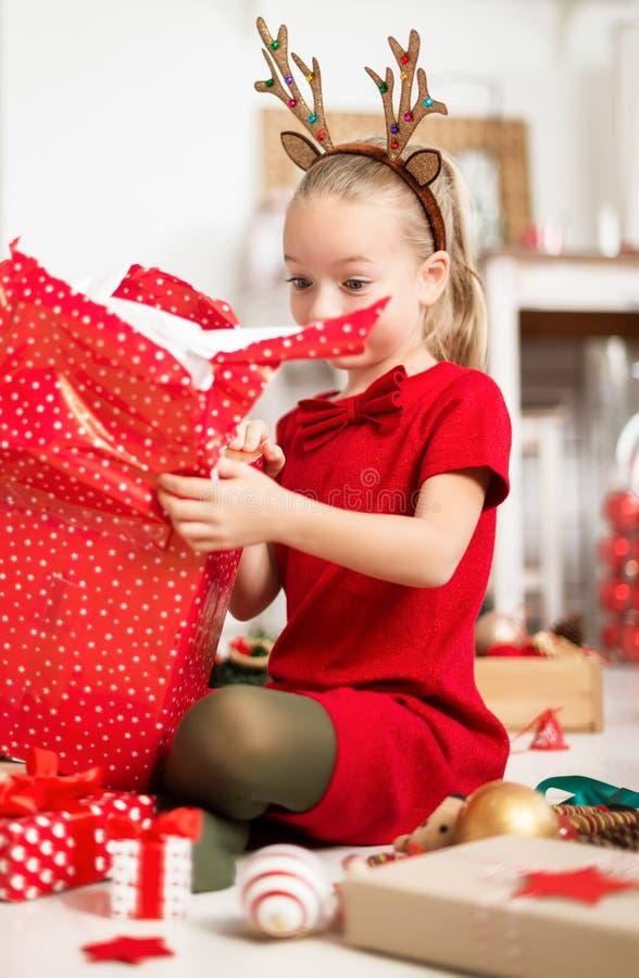 Moça entusiasmado super bonito que abre o grande presente de Natal vermelho ao sentar-se no assoalho da sala de visitas Tempo cân foto de stock royalty free