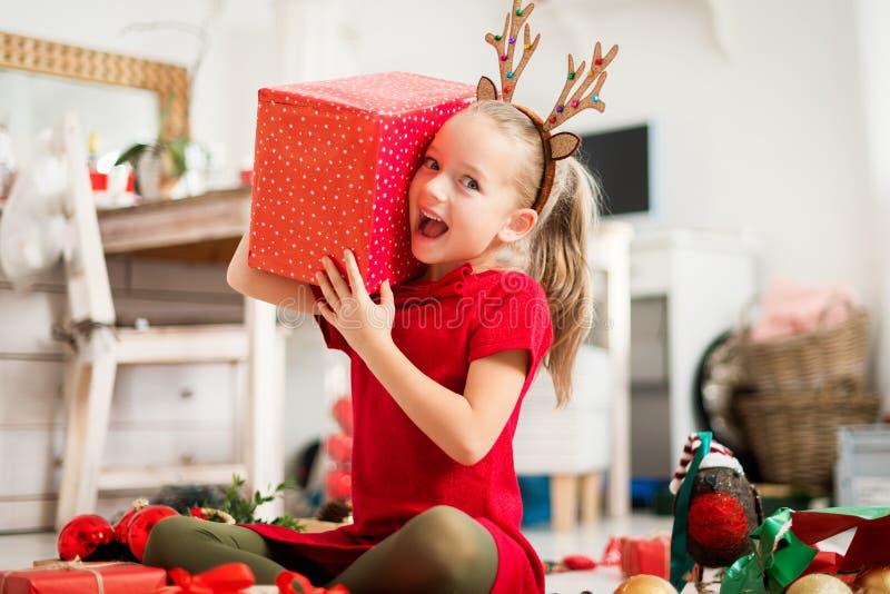 Moça entusiasmado super bonito que abre o grande presente de Natal vermelho ao sentar-se no assoalho da sala de visitas Tempo cân fotos de stock royalty free