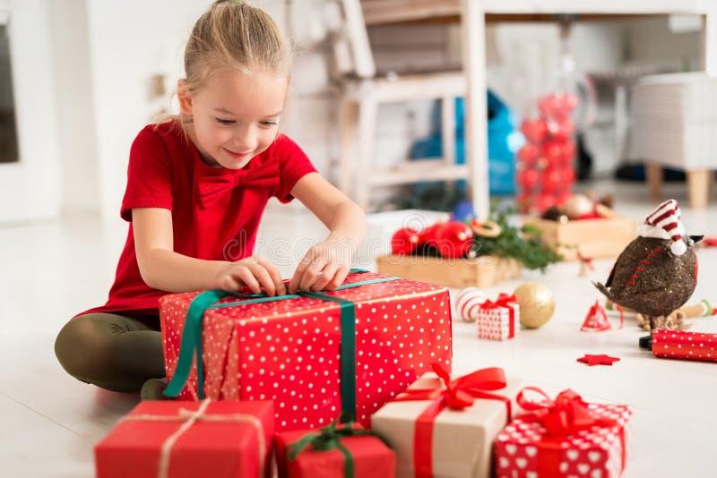 Moça entusiasmado super bonito que abre o grande presente de Natal vermelho ao sentar-se no assoalho da sala de visitas Tempo cân imagens de stock