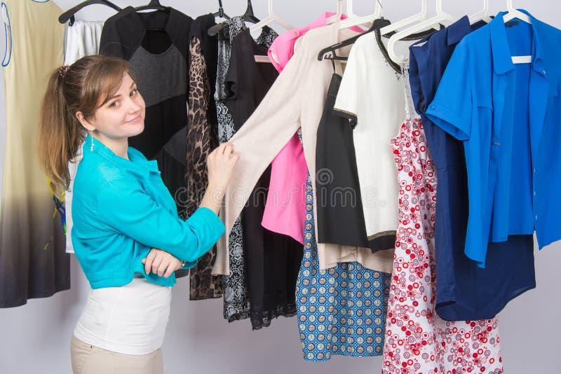 A moça escolhe a roupa no vestuário, e olhado no quadro imagens de stock royalty free