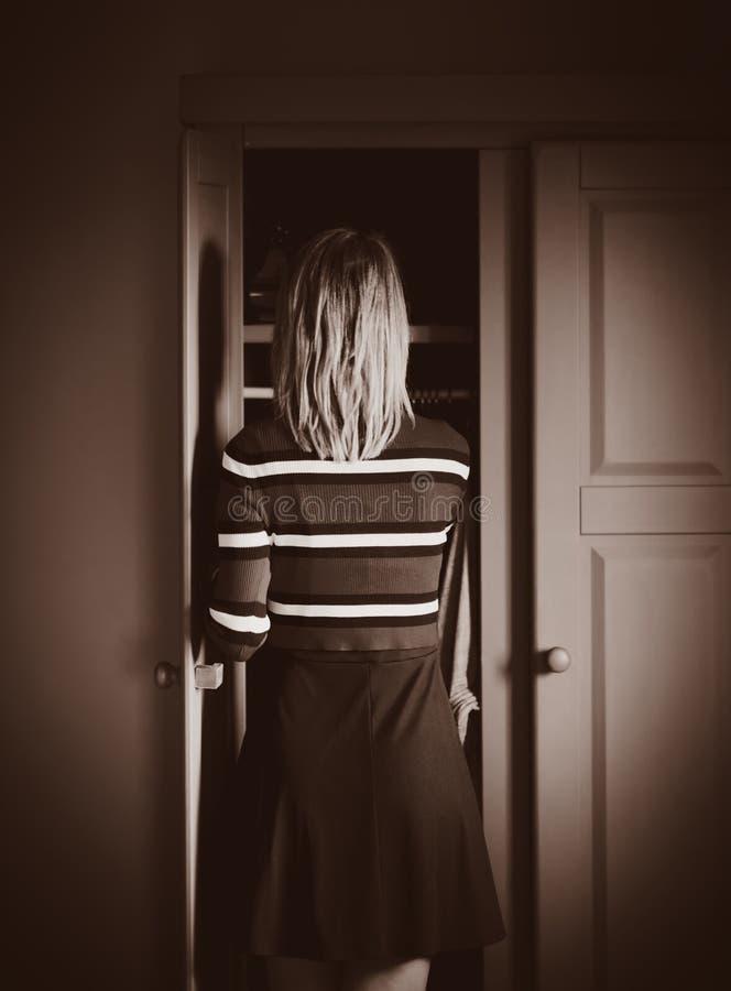 A moça escolhe uma camiseta em casa perto do vestuário imagens de stock royalty free