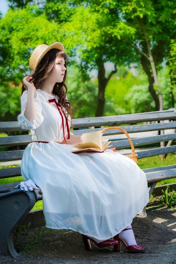 A moça está lendo um livro que senta-se em um banco imagens de stock