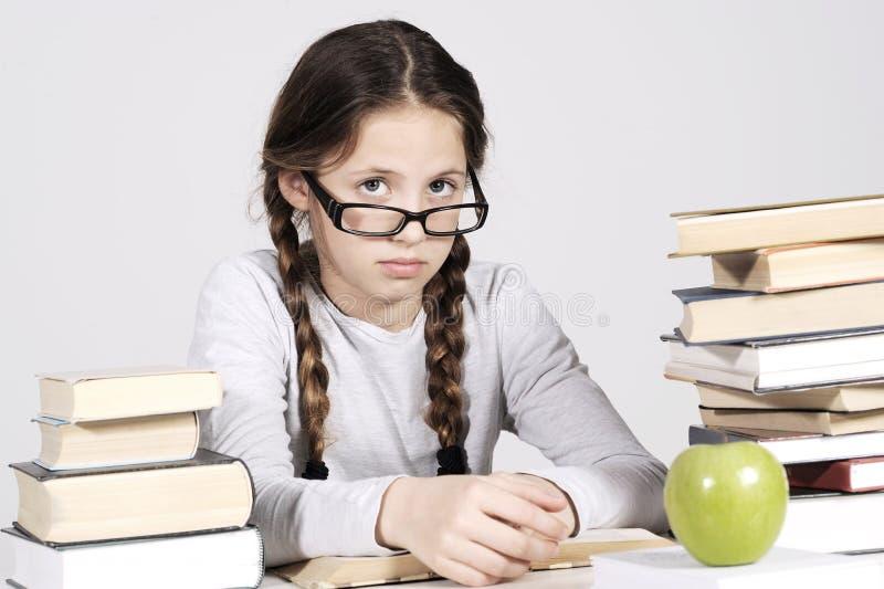A moça está sentando-se em sua mesa entre livros fotografia de stock royalty free