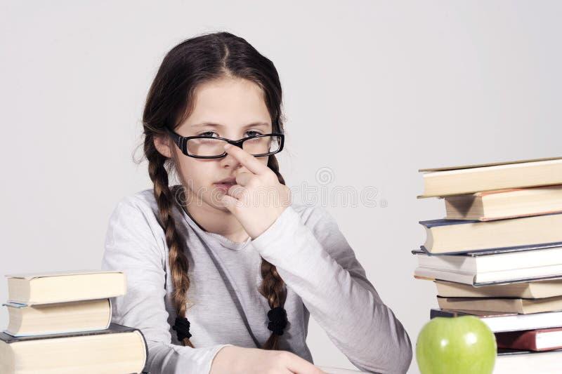 A moça está sentando-se em sua mesa entre livros imagem de stock royalty free