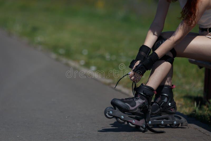 A moça está vestindo equipamentos para patinar no dia ensolarado morno fotografia de stock royalty free