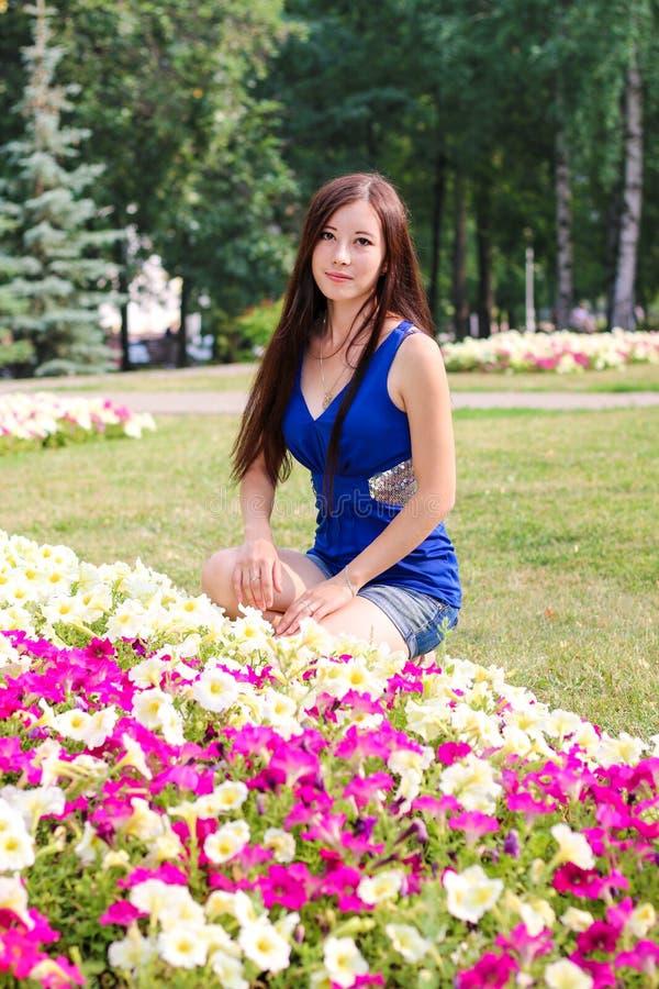 A moça, estudante, senta-se perto das flores no parque foto de stock royalty free