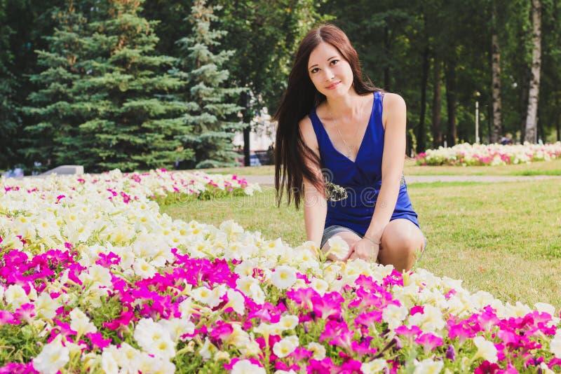A moça, estudante, senta-se perto das flores no parque fotografia de stock royalty free