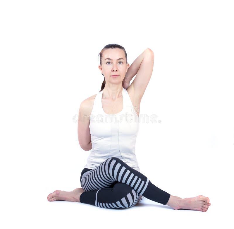 A moça executa poses diferentes da ioga, modelo bonito flexível em um fundo branco meditação e asanas imagens de stock royalty free