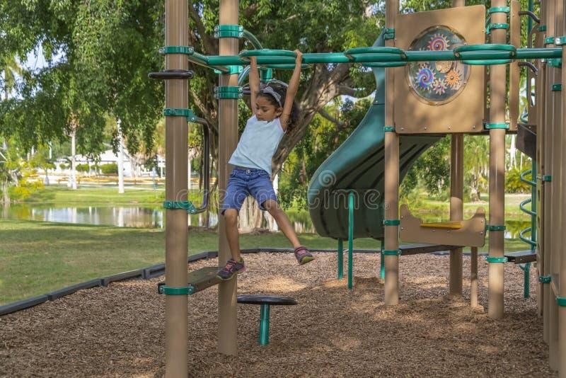 A moça fá-lo à extremidade enquanto balança através das barras no gym de selva exterior fotografia de stock royalty free