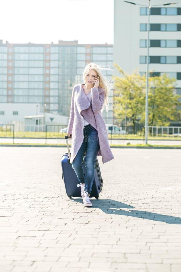 A moça fala em um telefone celular e vem com uma mala de viagem T fotografia de stock royalty free