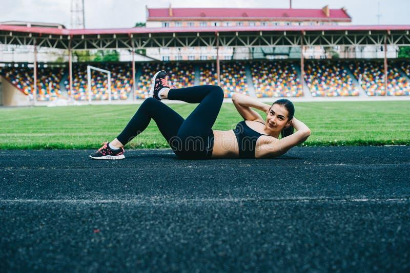 A moça faz exercícios no estádio fotografia de stock