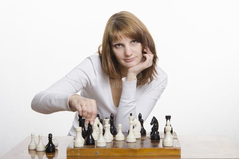 A moça faz um movimento, jogando a xadrez fotografia de stock royalty free