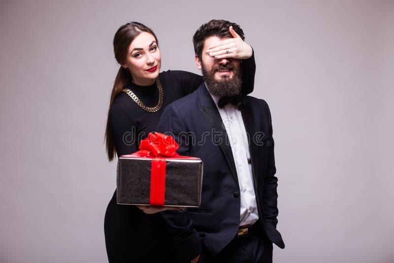 A moça faz um presente da surpresa para seu noivo fotos de stock