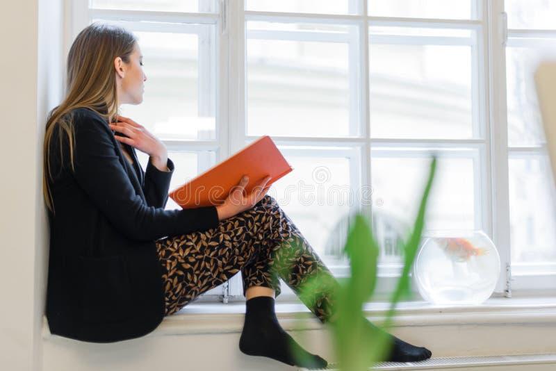 Moça feliz bonita que lê um livro na soleira imagem de stock
