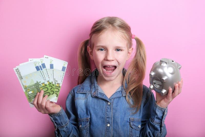 Moça feliz com as cédulas de prata do mealheiro e do euro no fundo cor-de-rosa Excepto o conceito do dinheiro fotografia de stock royalty free