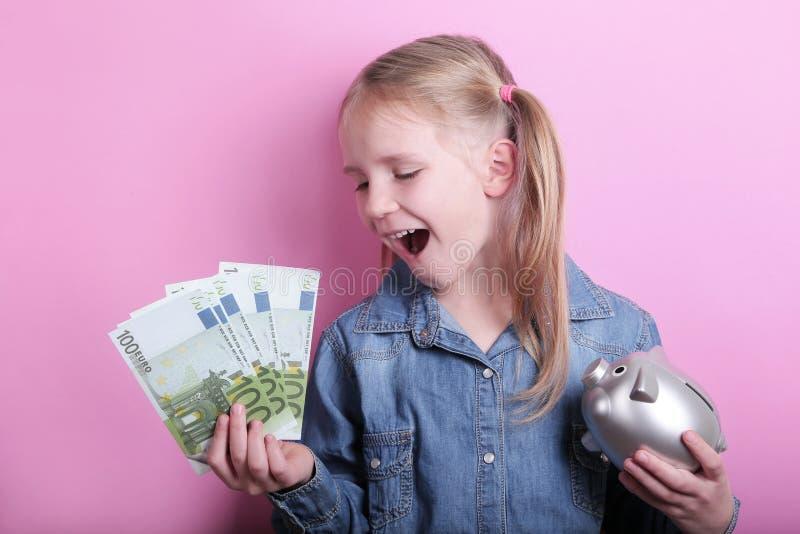 Moça feliz com as cédulas de prata do mealheiro e do euro no fundo cor-de-rosa Excepto o conceito do dinheiro imagem de stock royalty free