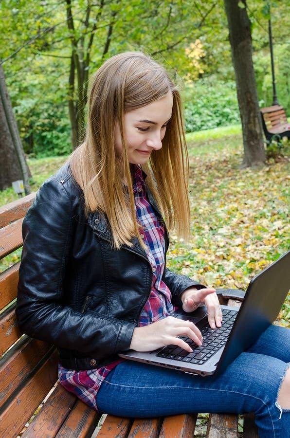 Moça feliz com portátil fora imagem de stock