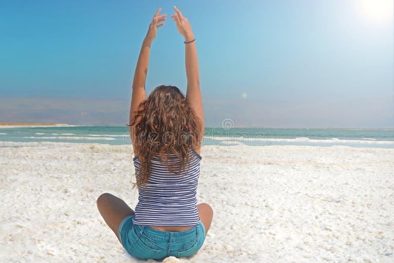 a moça feliz com suas mãos está travando a energia do sol a menina de cabelos compridos senta-se na costa do Mar Morto azul em Is foto de stock