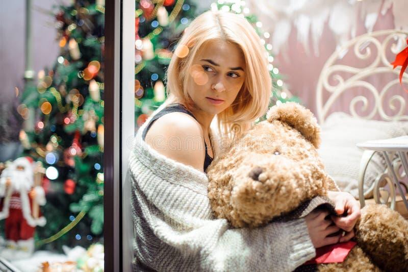 Moça feliz com um urso de peluche perto de uma árvore de Natal decorada Ano novo imagens de stock