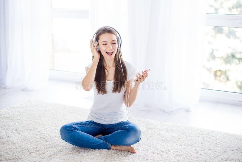 A moça feliz está apreciando a escuta a música com headpho foto de stock royalty free
