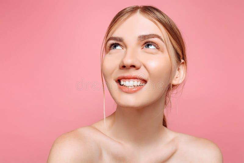 Moça feliz, menina com pele perfeita em um fundo cor-de-rosa Beleza e conceito dos cuidados com a pele imagem de stock