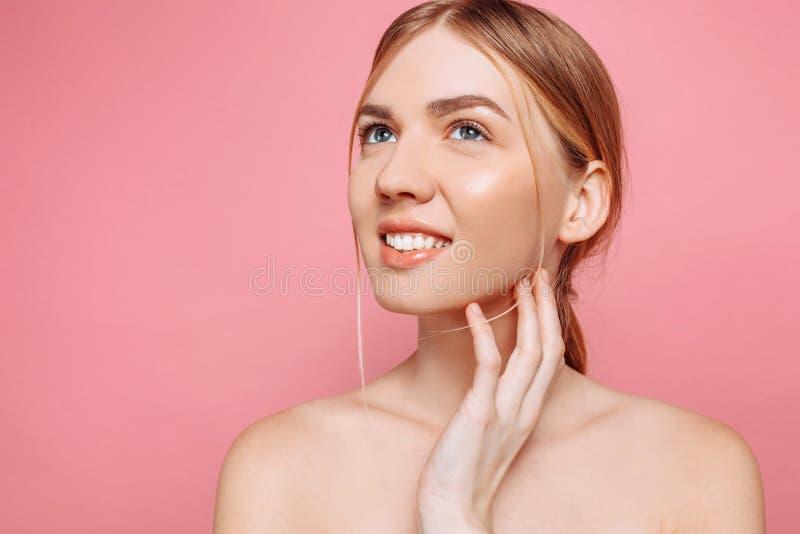 Moça feliz, menina com pele perfeita em um fundo cor-de-rosa Beleza e conceito dos cuidados com a pele foto de stock royalty free