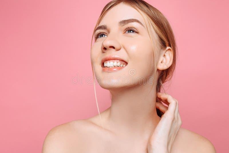 Moça feliz, menina com pele perfeita em um fundo cor-de-rosa Beleza e conceito dos cuidados com a pele fotos de stock