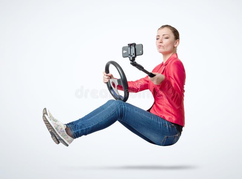 Moça feliz nas calças de brim e um revestimento vermelho que conduz um carro e que faz o selfie com um smartphone, em claro - fun foto de stock