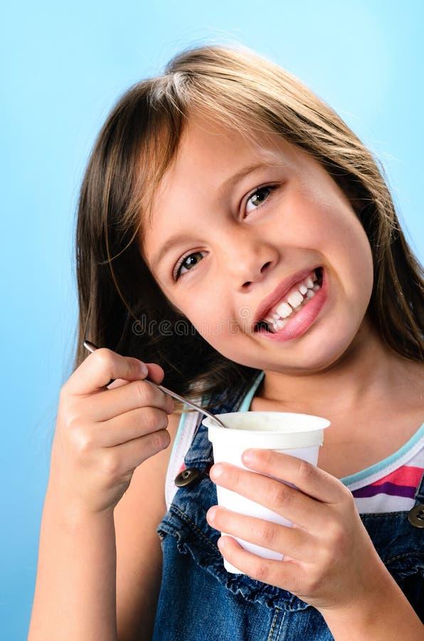 Moça feliz que come o iogurte probiótico foto de stock