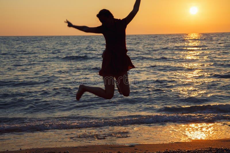 Moça feliz que salta contra o nascer do sol na praia fotos de stock royalty free