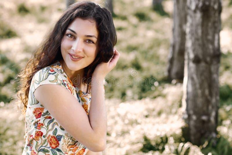 Moça feliz que senta em um início de uma sessão a floresta, luz solar brilhante ao redor, beleza da natureza na mola fotos de stock royalty free