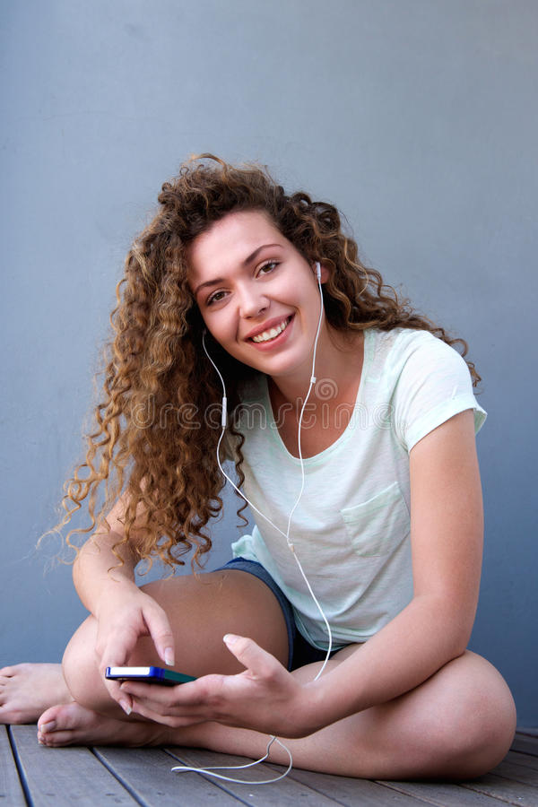 Moça feliz que senta-se no assoalho que escuta a música fotografia de stock