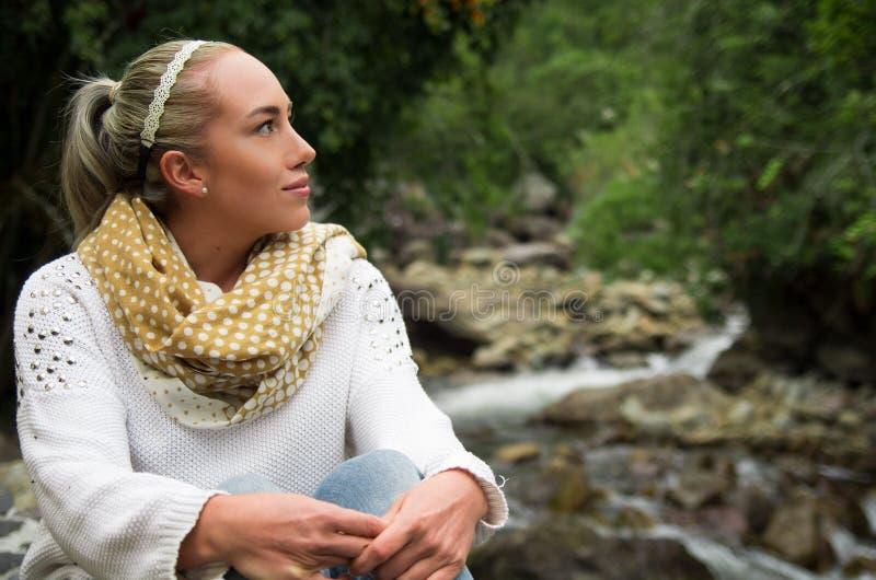 Moça feliz que senta-se pelas rochas em uma floresta que aprecia a tranquilidade imagem de stock royalty free