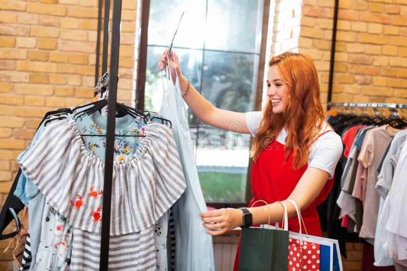 Moça feliz que sorri ao tomar o vestido longo na loja imagens de stock