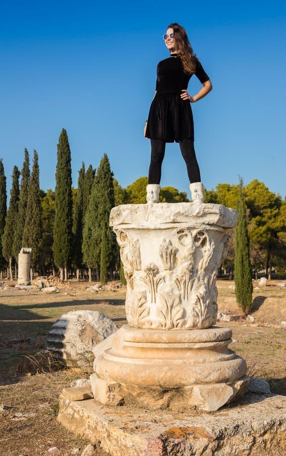 Moça grega bonita que guarda uma embarcação antiga no teatro antigo da ilha de Thassos, Grécia foto de stock
