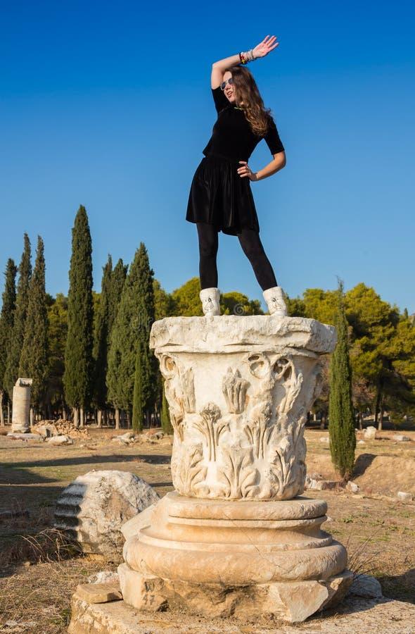 Moça grega bonita que guarda uma embarcação antiga no teatro antigo da ilha de Thassos, Grécia fotos de stock