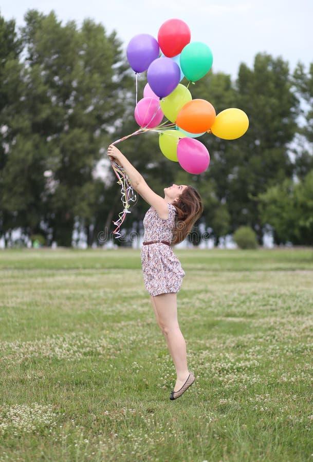 A moça guarda muitas tomadas coloridos dos balões foto de stock royalty free