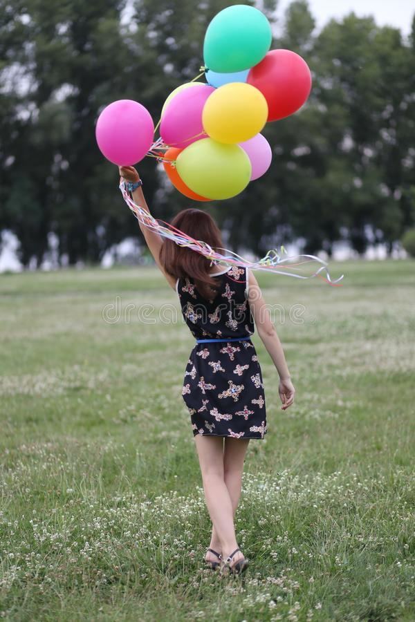 A moça guarda muitas tomadas coloridos dos balões imagens de stock royalty free