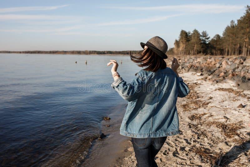 A moça inacreditavelmente atrativa está andando perto do beira-mar com fones de ouvido sem fio sobre, está dançando a e está apre imagem de stock