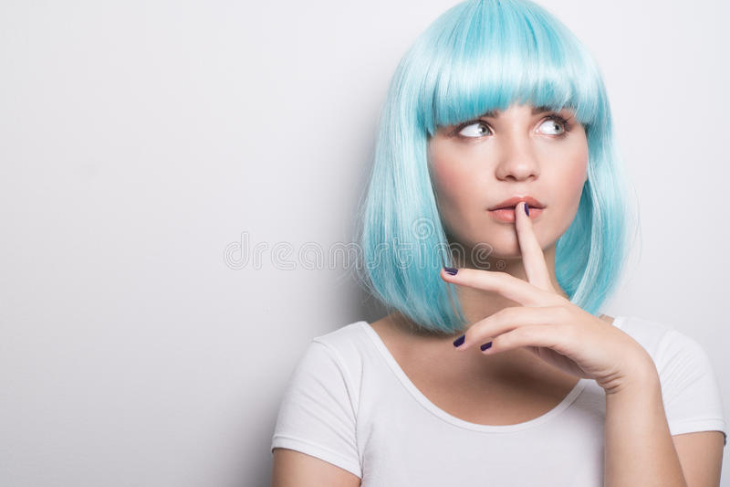 Moça insolente no estilo futurista moderno com peruca azul que pensa sobre o branco foto de stock royalty free