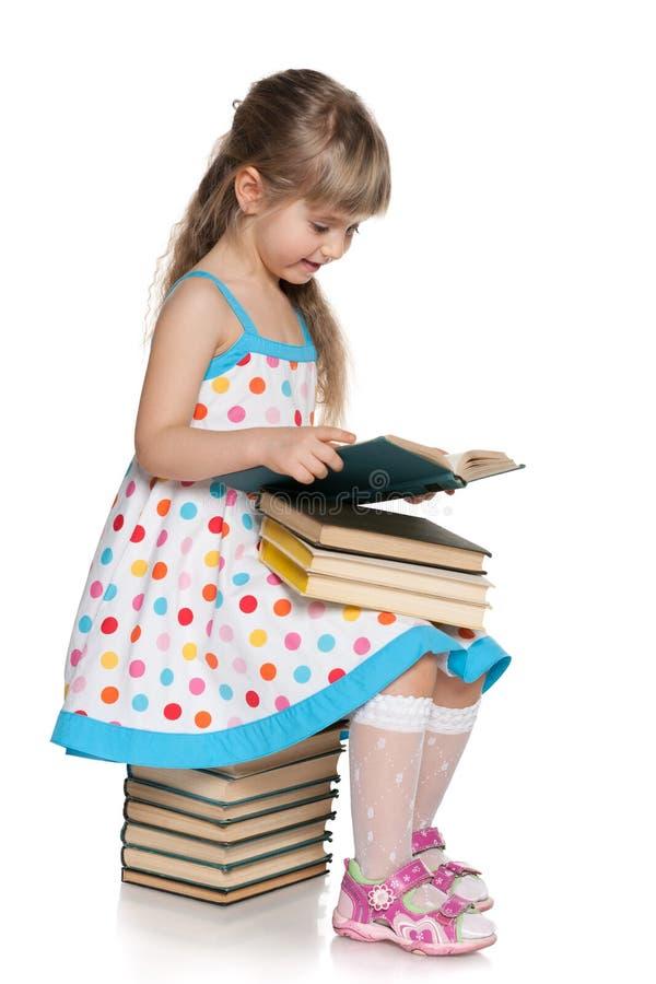 A moça lê na pilha dos livros fotos de stock