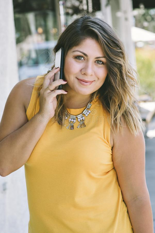 A moça latino-americano guarda um telefone celular a sua orelha ao sorrir e forma milenar feliz ocasional foto de stock