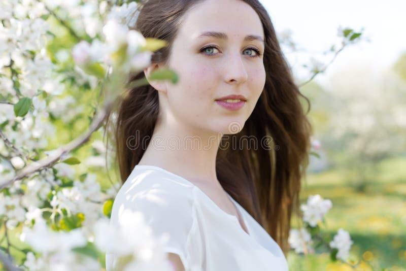 Moça macia consideravelmente doce com um sorriso brilhante com cabelo louro longo entre as árvores de maçã de florescência imagem de stock