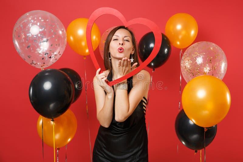 Moça macia no vestido preto que guarda o coração de madeira vermelho grande, bordos de sopro, enviando o beijo do ar no ar vermel fotos de stock