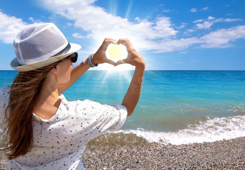 Moça moreno que guarda as mãos no sol de ajuste de quadro da forma do coração na praia do mar imagens de stock