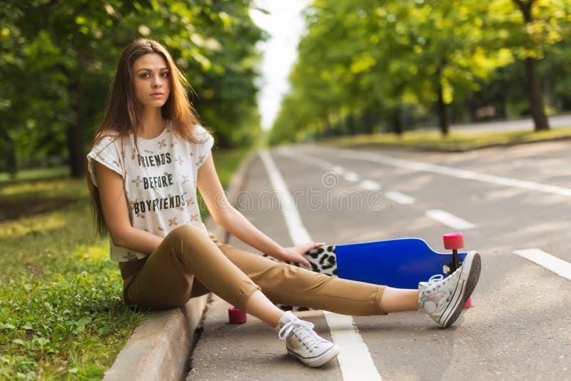 A moça muito bonita com o cabelo longo que senta-se no parque na trilha e mantém o lorgbord skateboarding lifestyle imagens de stock