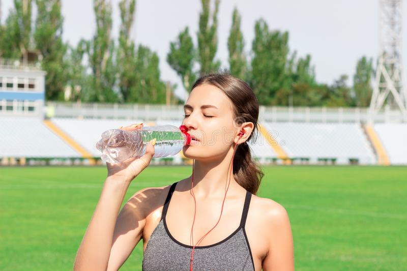 Moça na água cinzenta da bebida do sportswear e música de escuta após teaining mulher que está e que bebe com a garrafa no estádi foto de stock